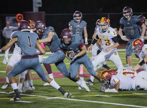 Shane Lythgoe bangs out a run into Estancia's secondary on Laguna's first touchdown drive behind blocking by Curtis Harrison and Adam Armstrong.
