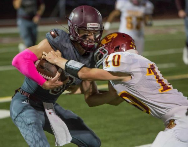 Curtis Harrison collides with Estancia's running back/defensive back, Trevor Pacheco, on a quarterback keeper.