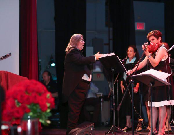 A musical director leads entertainers, part of the celebration last month.