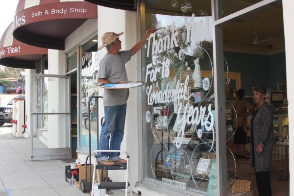 Artist Walter Visolay paints a farewell message outside a hotel tenant.