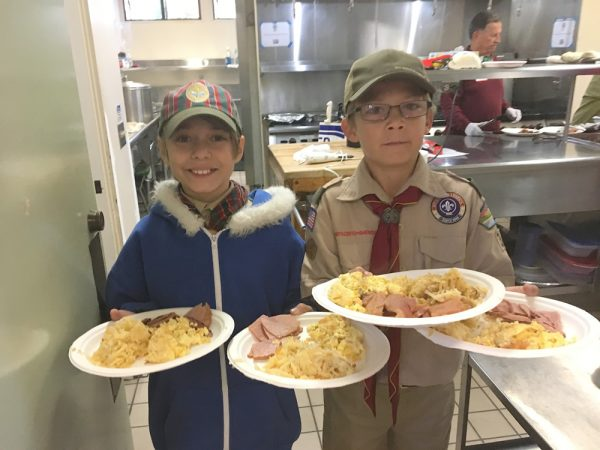 Mason Bruderer, left, and Elliott Leeds along with 14 other scouts from Laguna Beach Boy Scout troops 35 and 38 serve up ham, eggs and potatoes to a roomful of people without permanent homes this past weekend at the Laguna Presbyterian Church. Photo courtesy of Clay Leeds.