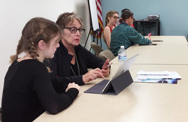 LBHS student Destiny Thompson, left, shows June Levinson how to navigate a tablet computer at the Susi Q. Register at 949-464-6645 for future Cyber-Senior tutorials Jan. 17 and 31. Photo by Joann Ekblad.