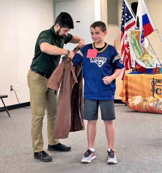 Football fan Gage Lee slips into a different uniform, the robe of Father Junipero Serra, founder of the California missions.