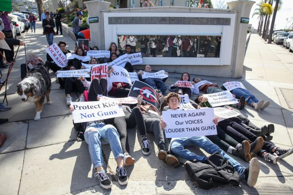 Students lay along the sidewalk of Park Avenue to protest gun violence during the national student walkout on Wednesday morning. Photo by Allison Jarrell
