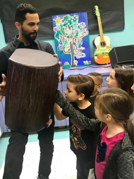 A musician demonstrates drumming with Boys and Girls Club members.