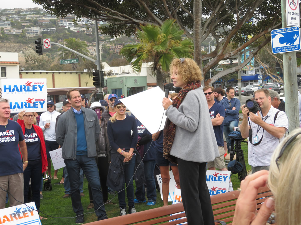 City Council member Toni Iseman, right, expresses her support for Harley Rouda, center left, campaigning on Main Beach in his hometown this past Sunday, May 20. The Democrat and 14 other candidates vie for voters in the June 6 primary, bidding to win the chance to challenge District 48 incumbent Rep. Dana Rohrabacher in the midterm election in November. Photo by Doug Miller.