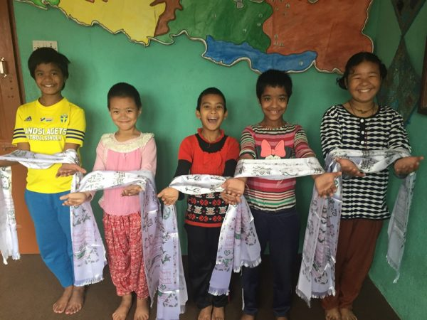 Girls from the Chhahari home with khatas, scarves offered in gratitude and respect. Each guest at Sunday's party will receive one.Photo by Christine Casey.