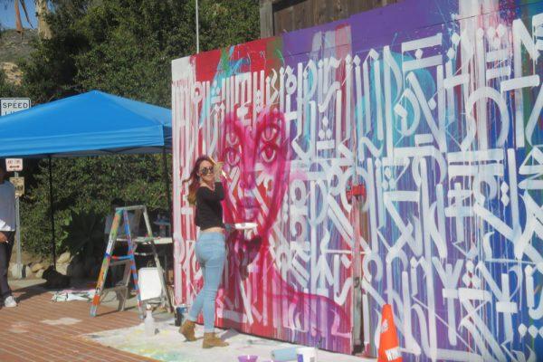 Artist Charmaine Olivia painting the mural earlier.