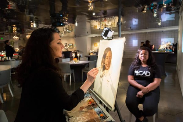 Hope Railey, chair of LCAD's fine art department, paints a portrait of senior Sureya Davis during the fundraising gala. Photo by Carol Covarrubias.