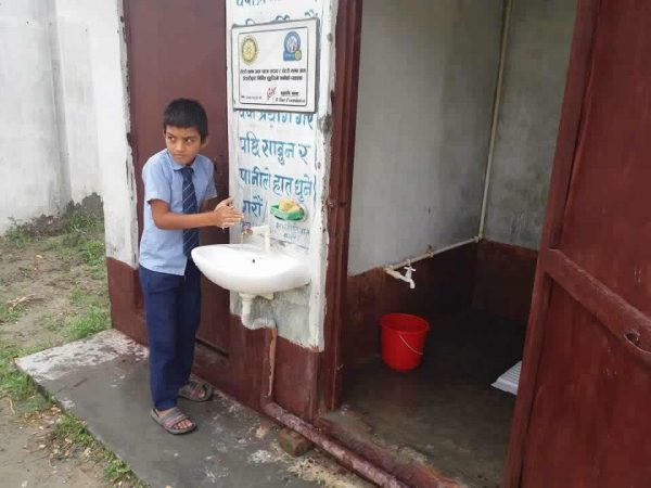 "A student takes advantage of a ""sanitation station"" outside restrooms installed by R Star Foundation, which received recognition on a plaque above the sink."