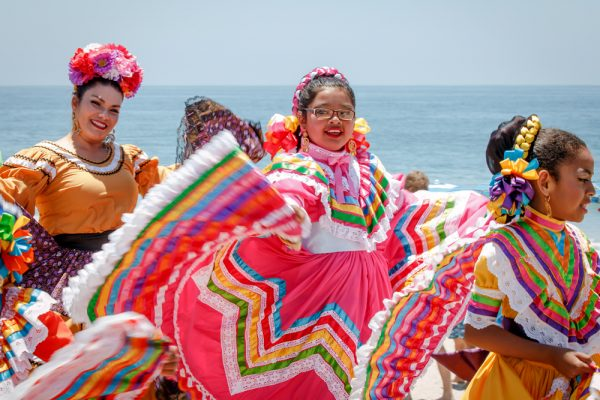 Corazones Alegres folkloric group dances on the Main Beach boardwalk.