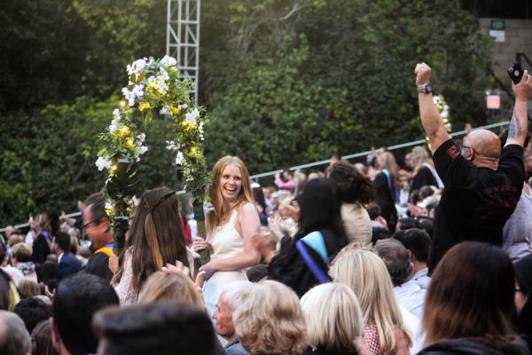 Members of the audience cheer as seniors enter the commencement ceremony through flowered arches.