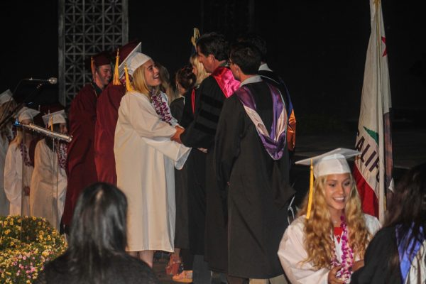 Graduates receive diplomas and congratulations from LBHS faculty.