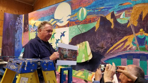 : Laguna artist David Cooke talks with reporters on June 4 as he works on recreating a 40-foot-long mural in Santa Monica by artist Millard Sheets.