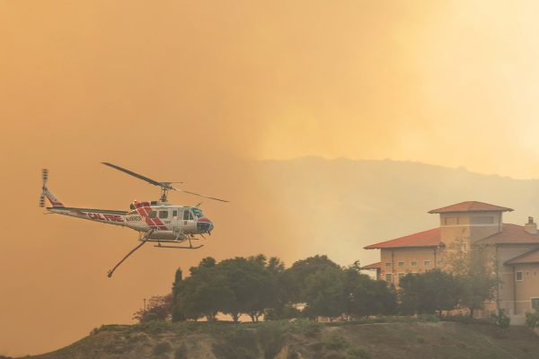 A helicopter makes a water drop during the June 2 fire near Soka University in Aliso Viejo, which borders the Aliso Wood Canyon Wilderness Park. Photo by Mark Golter