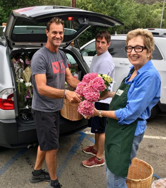Pantry volunteers, from left, Rino Zacurri, Ryan McCloskey, and Sharon McErlane receive a load of flowers and food donated by a local market. Photo by Kristy Melita.