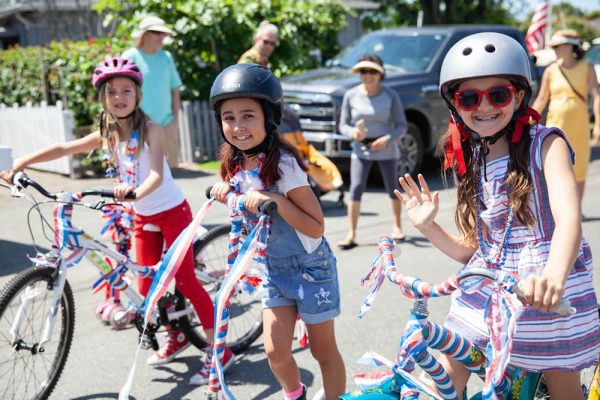 A trio of young cyclists smile for the camera during the annual Brooks Street parade.