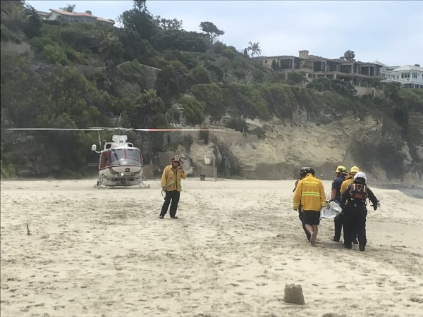 A swimmer identified by the coroner's office as Brian Riggs, 52, of Mission Viejo, is carried to a helicopter on Thousand Steps Beach on Saturday, July 14. Photo courtesy LBPD