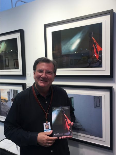 "Laguna photographer Jeff Rovner poses with his photograph, ""Yangon, Monastery Myanmar,"" and a copy of the anthology of writings based on his image."