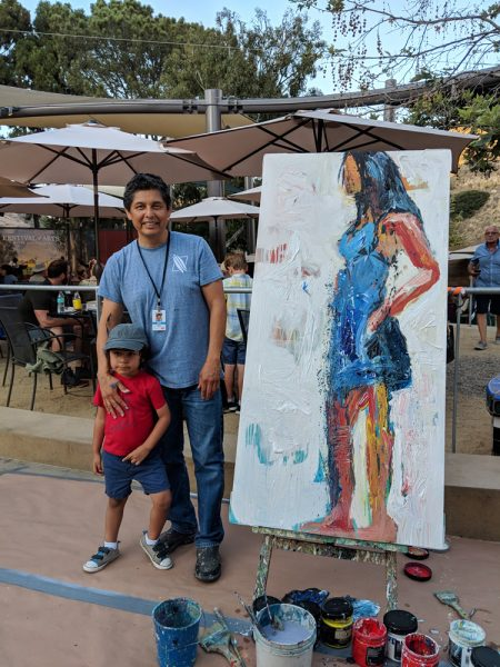 Hugo Rivera, seen here at the Festival of Arts with his son, has moved his gallery to a larger suite at 550 S. Coast Highway. Photo: courtesy