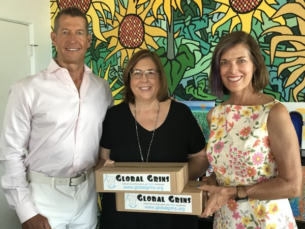 Global Grins founders and Laguna Beach residents Todd Miller (left) and Joselyn Miller (right) present their one-millionth toothbrush delivered to Kristen Point (center), director of development and marketing for the Friendship Shelter, on Aug. 10. Photo: courtesy