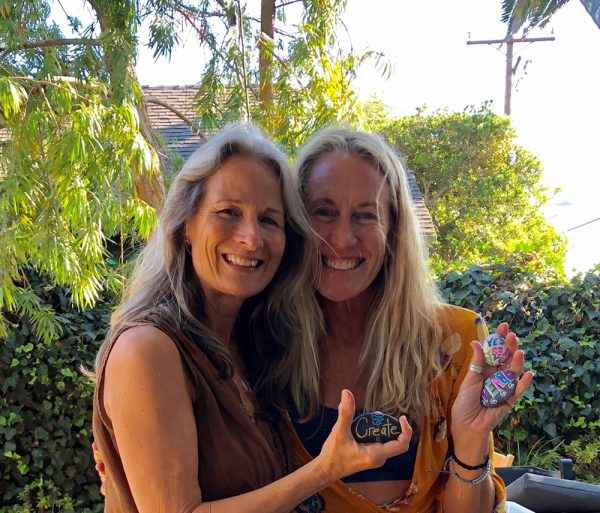 : Laguna Beach poet Lisa Hughes Anderson and Kristien Thomas with kindness rocks painted at the July launch party.